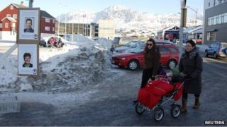 Locals walk past campaign posters in the centre of Nuuk on Monday