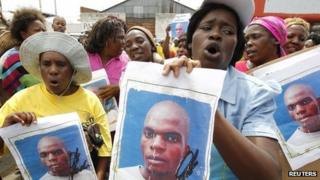 Protesters chant slogans as they carry posters of Mido Macia in Johannesburg on 8 March 2013