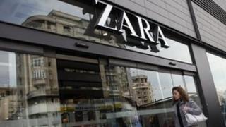 Woman walks past Zara store