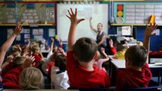 Children putting their hands up in class