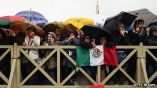 Pilgrims shelter from the rain as they watch for smoke on St Peter's Squar