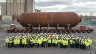 Members of staff at Berkeley's former nuclear power station stand in front of a giant boiler