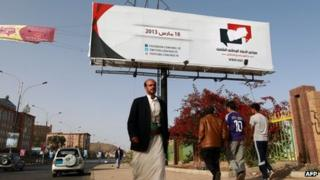 Men walk past a poster advertising the national dialogue conference in Sanaa (14 March 2013)