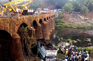 Rescuers and others gather at the site of a bus accident in Ratnagiri district, in the western Indian state of Maharashtra, Tuesday, March 19, 2013