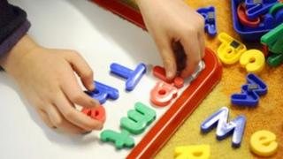 Child putting letters on board
