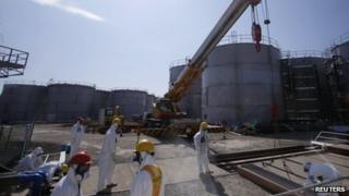 Workers wearing protective suits and masks are seen near tanks of radiation contaminated water at Tokyo Electric Power Company's (TEPCO) tsunami-crippled Fukushima Daiichi nuclear power plant in Fukushima prefecture March 6, 2013