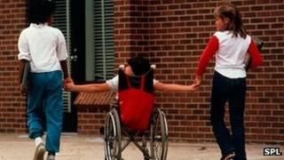 Physically handicapped child holds hands with friends