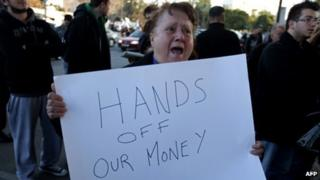 A Cypriot woman shouts slogans as she holds a placard during a protest against an EU bailout deal outside the parliament in Nicosia on 19 March 2013