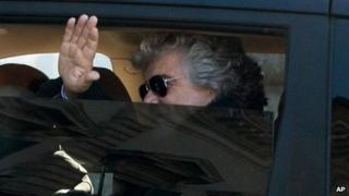 Five Star Movement leader Beppe Grillo waves from inside a car as he arrives for talks with Italian President Giorgio Napolitano on 21 March 2013