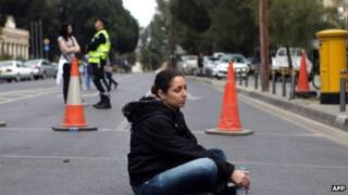 An employee of Cyprus Laiki (Popular) Bank sits on the ground as protesters blocked the streets leading to the parliament in Nicosia on March 22, 2013