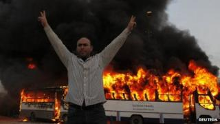 An anti-Morsi protester celebrates after Muslim Brotherhood buses were set on fire in Cairo. Photo: 22 March 2013