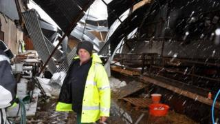 Farmer James McHenry surveys the damage caused to his sheds