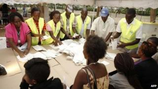 Poll officials count ballots at the polling centre of Kisumu Sports Ground, western Kenya, following Monday's general elections