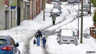 People walking on snowy road in N belfast