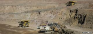 A digger and two ore trucks at the Oyu Tolgoi mine in Mongolia