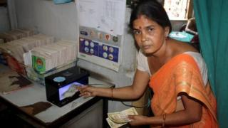 Seema Fokle with the machine that detects forged notes