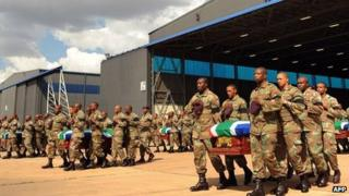 South African troops carry coffins of fallen colleagues at air force base near Pretoria - 28 March
