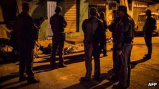 Police inspect the bodies of two men killed in the streets of Sao Paulo last week