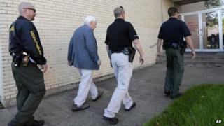 Kaufman county law enforcement officials escort an employee inside the county courthouse 1 April 2013 Kaufman, Texas