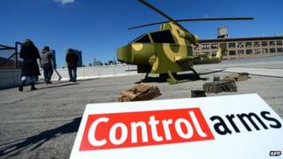 Arms treaty activists with replica of military helicopter. 27 March 2013