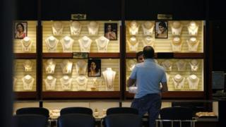 An Indian sales man attends to a customer at a jewelry store in Bangalore, India, Thursday, Feb. 28, 2013. In
