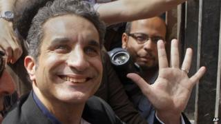 "Popular Egyptian television satirist Bassem Youssef, who has come to be known as Egypt""s Jon Stewart, waves to is supporters as he enters Egypt""s state prosecutors office"