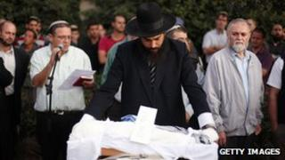Israeli settlers attend the funeral of Asher Palmer and his infant son, Yonatan, on 25 September 2011, near the West Bank town of Hebron.