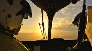 Pilots look out at setting sun while in flight