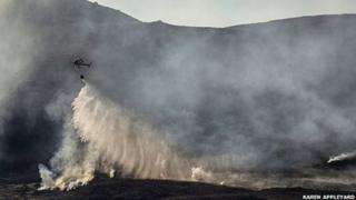 Helicopter releases water over hill fire