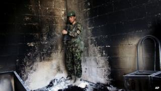 An Afghan army soldier stands guard in the destroyed courthouse in Farah