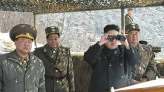 North Korean leader Kim Jong-un (C) watches what the country's media said was a drill of drone planes at an undisclosed location