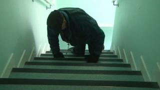 Alan Rutter crawling up the stairs