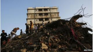 Rescue workers search through the rubble of a collapsed building in Thane, 5 April 2013