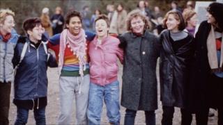 Women locking arms and singing at Greenham Common
