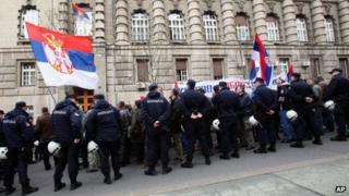 Protesters wave Serbian flags during a protest of Serbian nationalists in front of the government building in Belgrade, Serbia, 8 April 2013