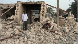 Man standing in rubble in Shonbeh, southern Iran (09/04/13)