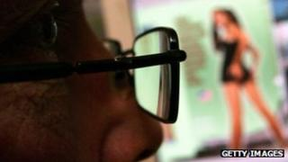 A man wearing glasses looks at a pornography website