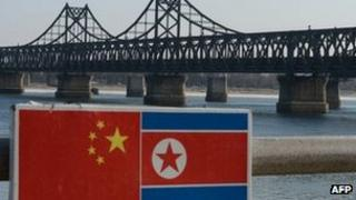 A sign displaying the Chinese (L) and North Korean (R) flags is pictured beside the Sino-Korean Friendship Bridge which leads to the North Korean town of Sinuiju, on the banks of the Yalu River, in Dandong on February 7, 2013.