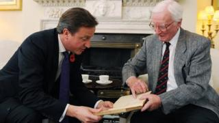 Leslie Valentine showing Prime Minister David Cameron the entry on the smoke laying operation in his pilot log book
