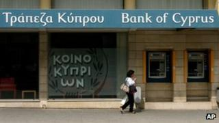 A woman passes outside a branch of Bank of Cyprus in the main shopping street in central capital Nicosia, Cyprus