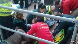Lifeguards attend injured kite surfer