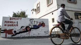 A foreign worker cycles past graffiti against holding the upcoming Formula 1 Grand Prix in Bahrain in the village of Barbar, west of the capital Manama, on March 31, 2013