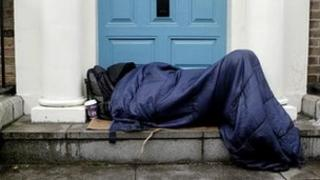A homeless person asleep in a doorway.