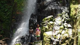 A boy and girl stand in front of the sacred waterfall