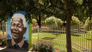 A mural portrait of former South African President Nelson Mandela is surrouned by a fence in Thokoza Park in Johannesburg, South Africa
