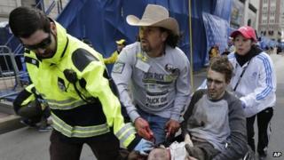 Medics help an injured man, named by media as Jeffrey Bauman, following an explosion in Boston, Monday, April 15, 2013