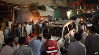 A destroyed vehicle at the site of a suicide bomb attack at an election campaign rally in Peshawar, 16 April 2013