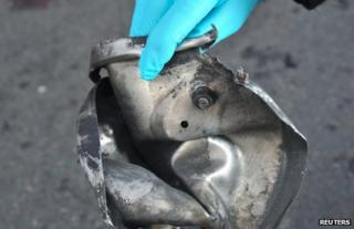 An investigator holds up a twisted piece of metal said to have been used in the Boston bombing, 16 April
