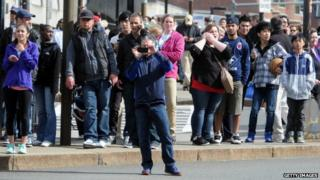 Crowd at the Boston Marathon; a man takes a picture with his phone