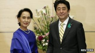 Nobel laureate and Burma opposition leader Aung San Suu Kyi (L) shakes hands with Japan's Prime Minister Shinzo Abe at Abe's official residence in Tokyo 18 April 2013.